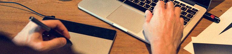 Close em uma mão trabalhando no notebook e uma mesa digitalizadora.